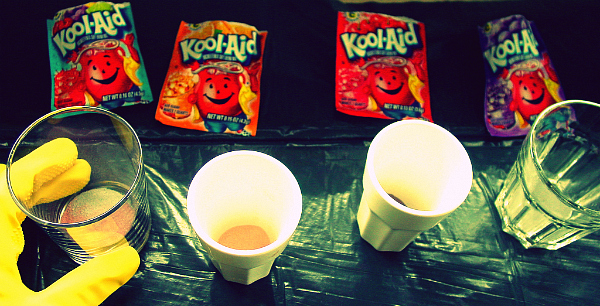 Rubber-gloved hand, four Kool-Aid packets, and some cups