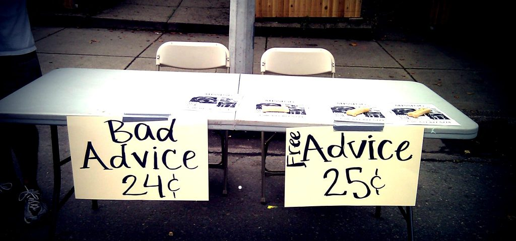 a table with two signs attached to the front: Bad Advice: 24 cents. Free Advice: 25 cents.